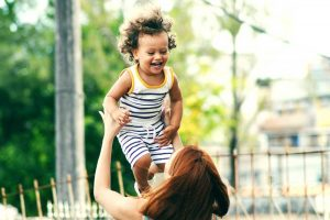 mother bouncing smiling child